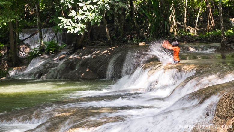 Дети играются на водопаде, Канчанабури, Таиланд