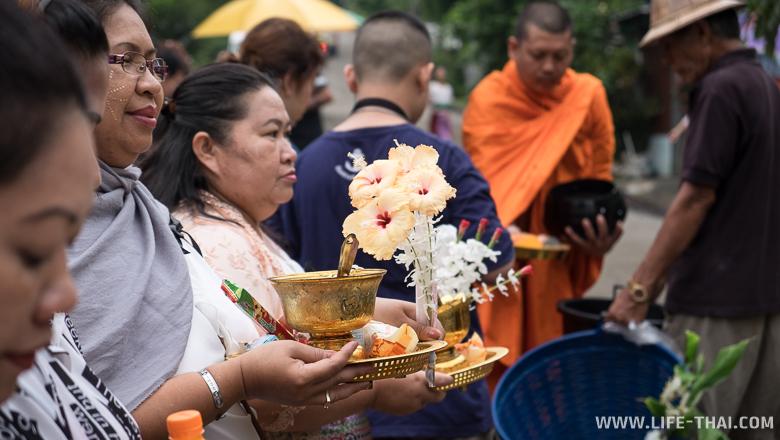 Люди отдают подаяние монаху и молятся, Таиланд