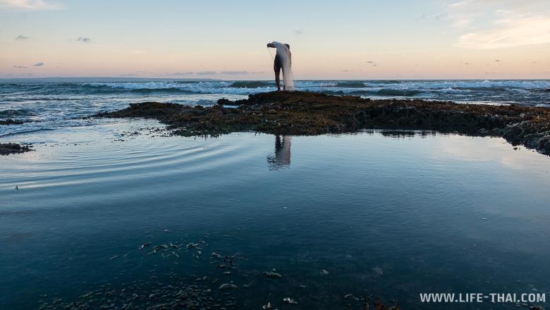 Рыбак с сетью на закате, пляж Сесех , Бали