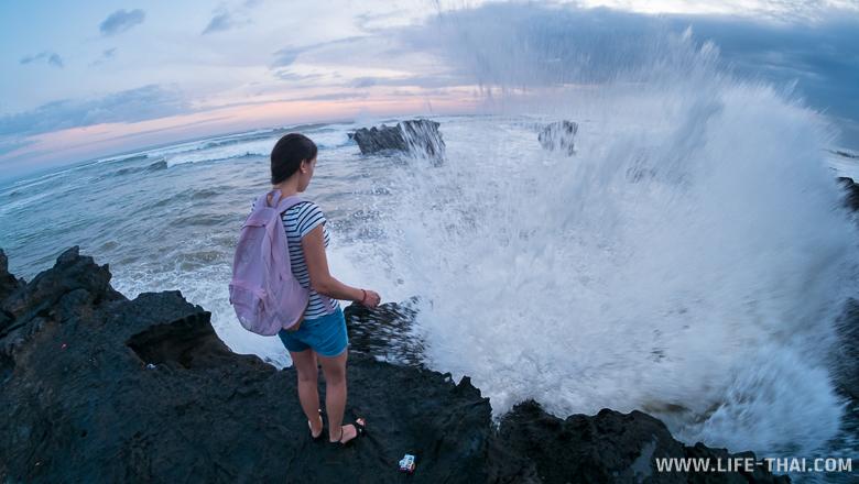 Волна разбилась о камни на Бали, Индонезия