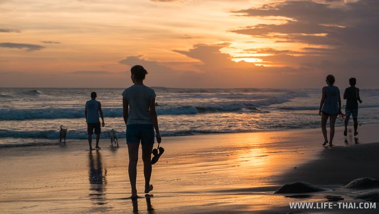 Люди на пляже на закате, Бали