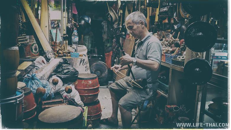 Мужчина в своей лавке играет на музыкальном инструменте