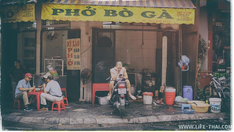 Вьетнамец сидит на мотобайке в кафе, Ханой