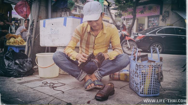 Молодой парень чистит обувь, а сзади него дорогая машина