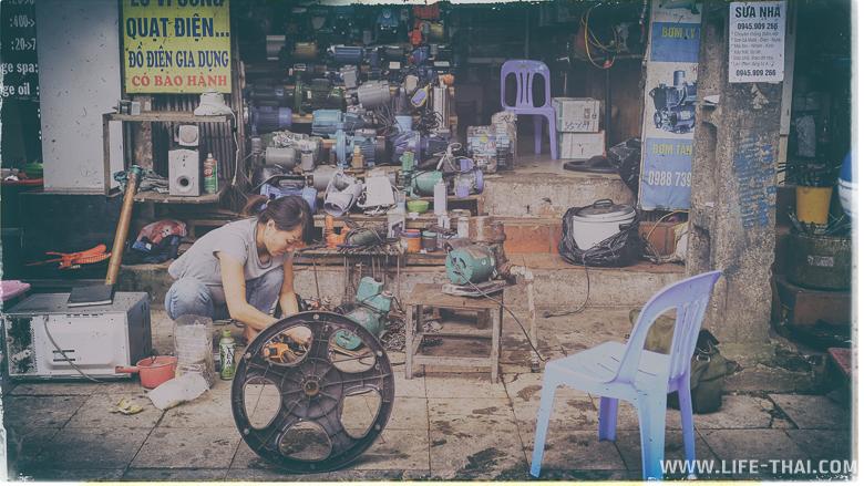 Женщина что-то чинит перед своим магазином