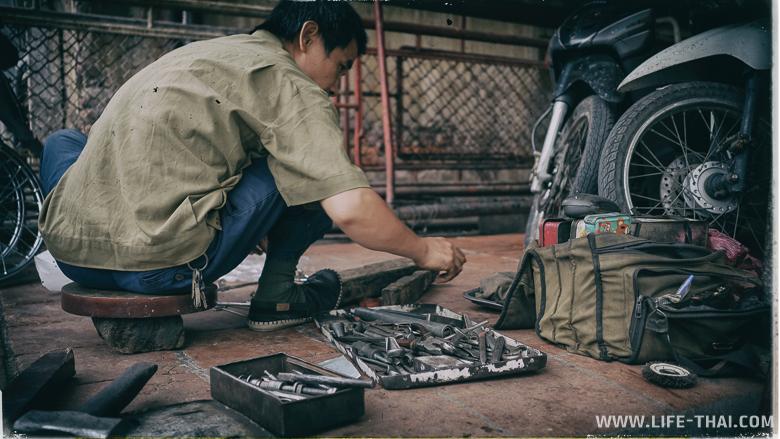 Вьетнамец что-то мастерит, улицы Ханоя, Вьетнам