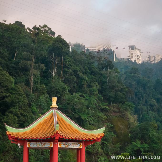 Китайская беседка и над ней пролетают кабинки канатной дороги - достопримечательность Куала Лумпура