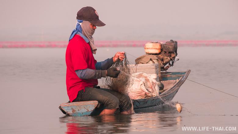 Рыбак на озере распутывает сети