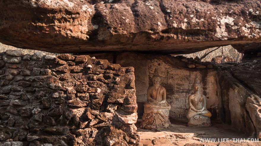 Статуи Будды под крышей из огромной каменной плиты