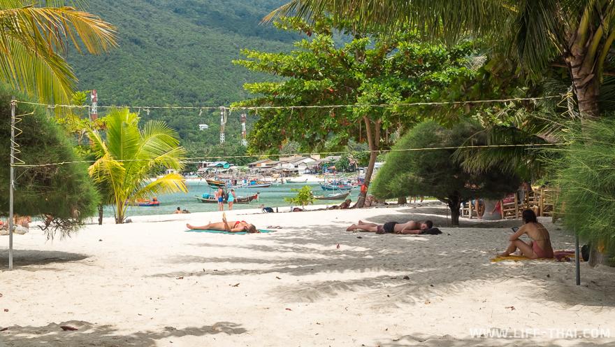 Люди отдыхают в тени на пляже Малибу