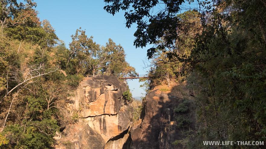 Человек стоит на мосту через каньон Оп Луанг