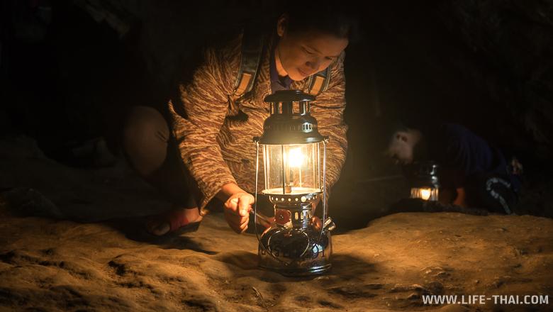 Женщина-гид подготавливает газовую лампу перед экскурсией в пещеру Тхам Лод