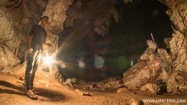 Гид подсвечиваает пещеру газовой лампой