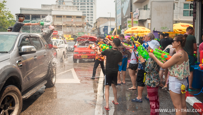 Люди на улице обливаются водой во время празднования тайского нового года в Чиангмае