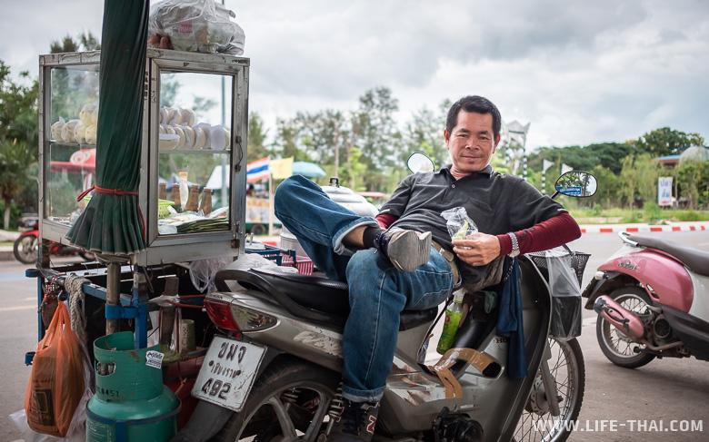 Мужчина обедает на мопеде в Пхаяо