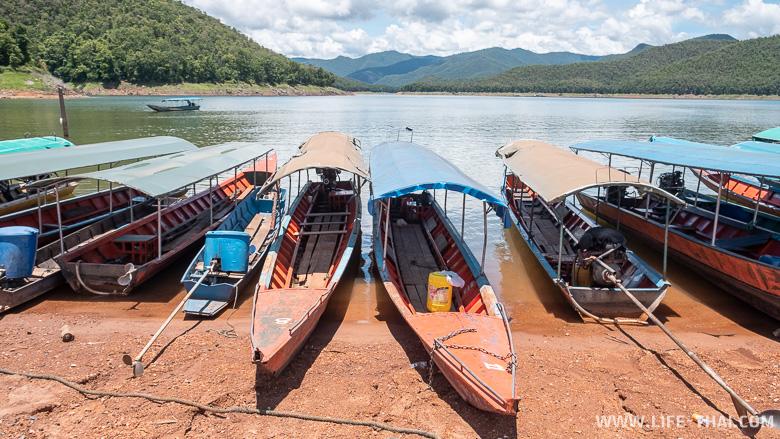 Лодки на берегу, которые везут к деревянным плавучим домикам