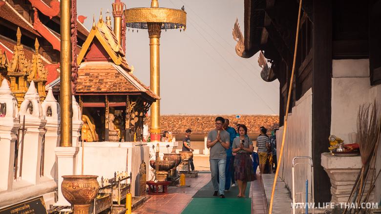 Тайцы ходят вокруг чеди в храме в Лампаге