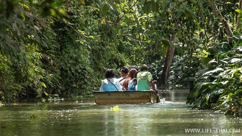 Люди в лодке плывут к пещере Tham Le Khao Kob, Транг