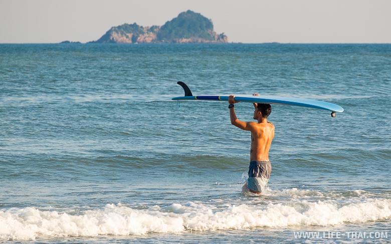 Таец с доской для серфинга заходит в море в Хуа Хине