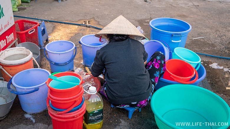 Вьетнамка моет посуду на улице