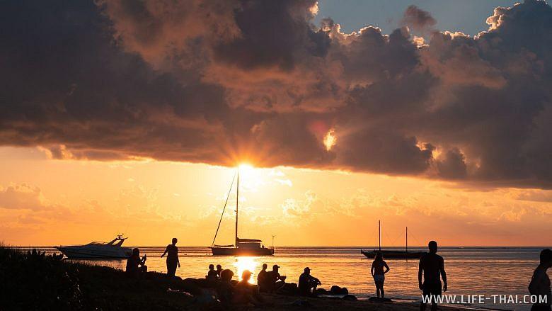 Люди на берегу на закате. Маврикий